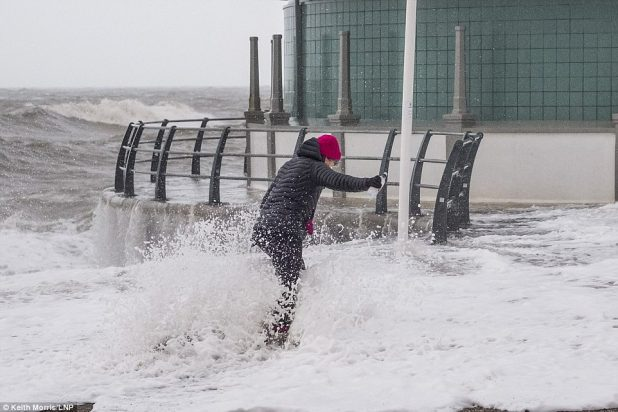 A woman will get caught in a wave this morning as Britain was once hit by solid westerly winds after Storm Eleanor the day gone by