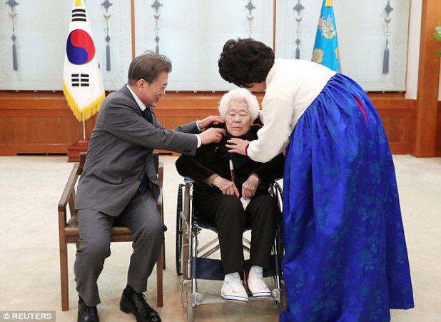 Helping hand: President Moon and first woman Kim Jung-Suk greet one among the surviving 'comfort girls folk' on Thursday