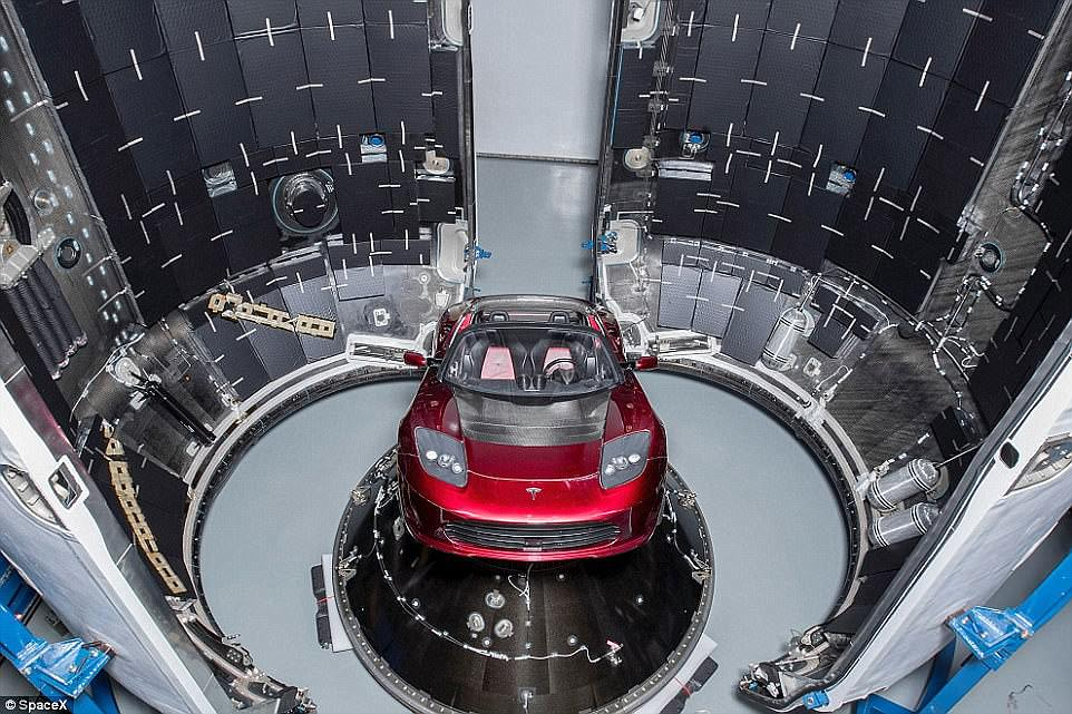 Musk said the launch vehicle will blast off at the 'end of the month' on an unmanned mission with a unique payload - the billionaire's cherry red 2008 Tesla Roadster, which will be fired toward Mars. Pictured is the car strapped into the Falcon Heavy's main module