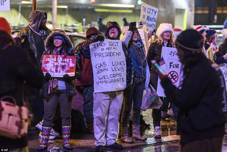 People hold signs in protest of President Donald Trump, outside of CNN Headquarters
