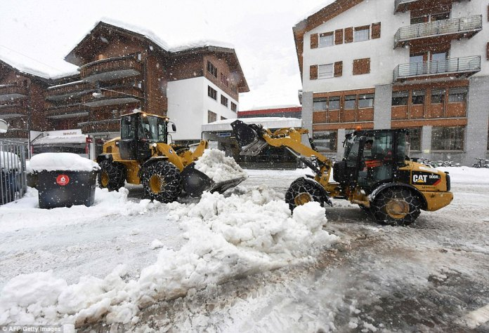 A reconnaissance flight is planned over the area to help determine the situation and how to proceed. Pictured: Tractors clearing snow near the train station