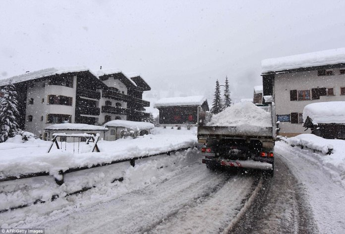 A number of other Valais villages were also isolated by the heavy snow. The Simplon region of Valais was hit by 3.5 feet of snow in a 24-hour period, the ATS news agency reported. Pictured: Workers clearing the snow outside Zermatt train station