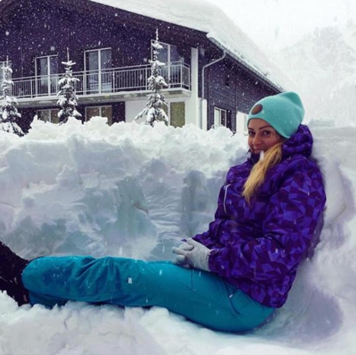 A woman enjoys a quiet moment in a snow trench as the ski resort of Zermatt is covered in the white stuff