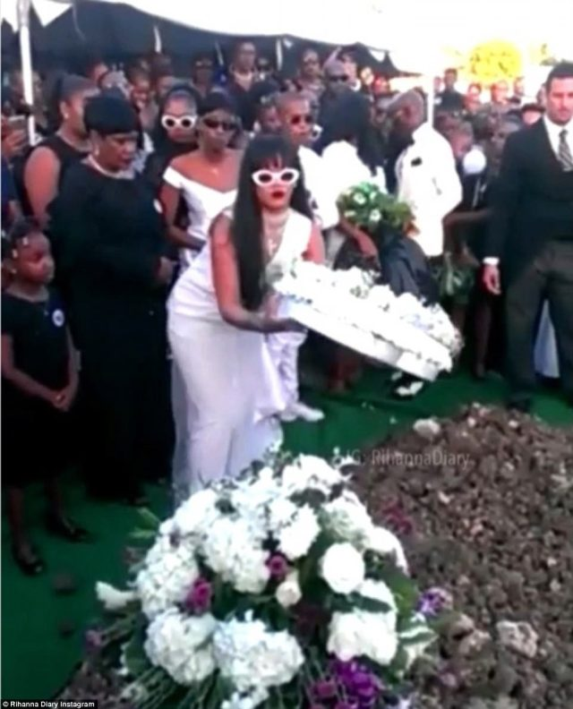 Laid to rest: Rihanna is pictured placing flowers on the grave of her cousin