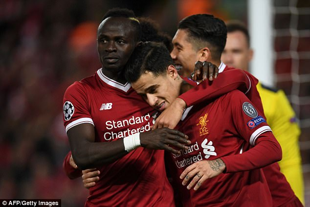 Coutinho is hugged by Sadio Mane (left) and Roberto Firmino after scoring a goal in December