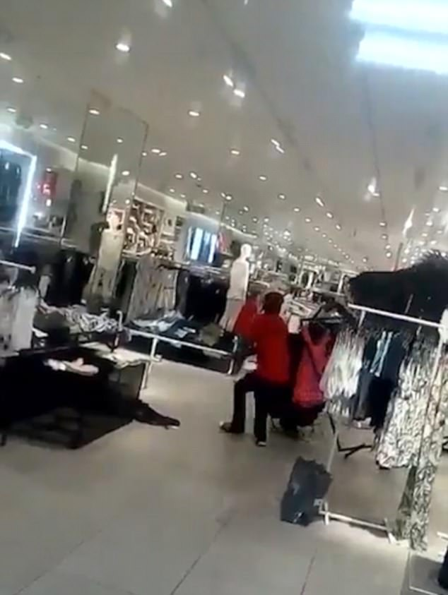 A red shirted activist is seen pulling over a display at theMenlyn Park store