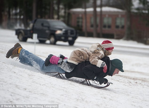 Berean Matthews, 11, rides on the back of her father, Steven Matthews, as they sled down a snowy hill on the campus of the University of Texas in Tyler on Tuesday