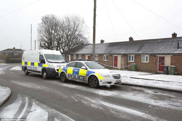 A police car and a police van parked outside a bungalow which was sealed off as a crime scene amid the snow on Sunday morning