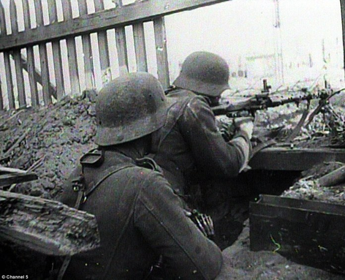 Two German soldiers hold their ground and take cover as they fire from a derelict building