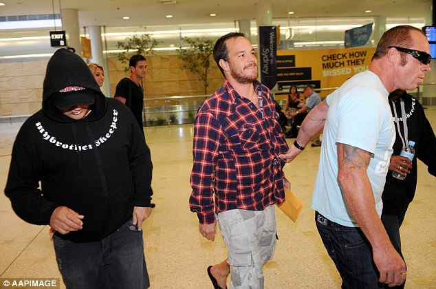Koby Abberton (centre) is led through Sydney Airport after being arrested in Honolulu in 2008