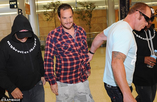 Professional surfer Koby Abberton (centre) arrives in Sydney after being arrested in Hawaii
