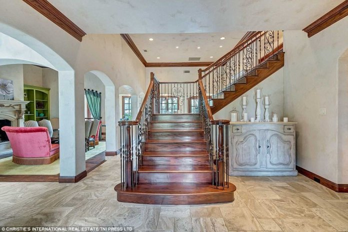 Stunning stairway: On entering the home, guests are greeted by a grand wooden staircase, which sweeps into the living area
