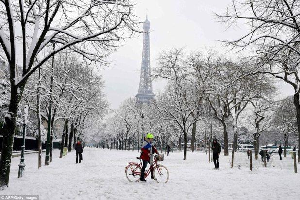 Continuando: los viajeros de la mañana se abren paso a través del callejón cubierto de nieve del Champ de Mars cerca de la torre Eiffel