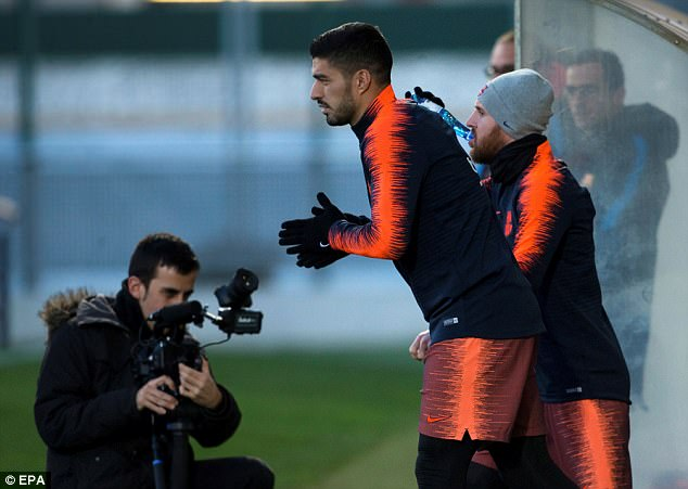 Luis Suarez and Lionel Messi wrapped up warm for training with their Barcelona team-mates