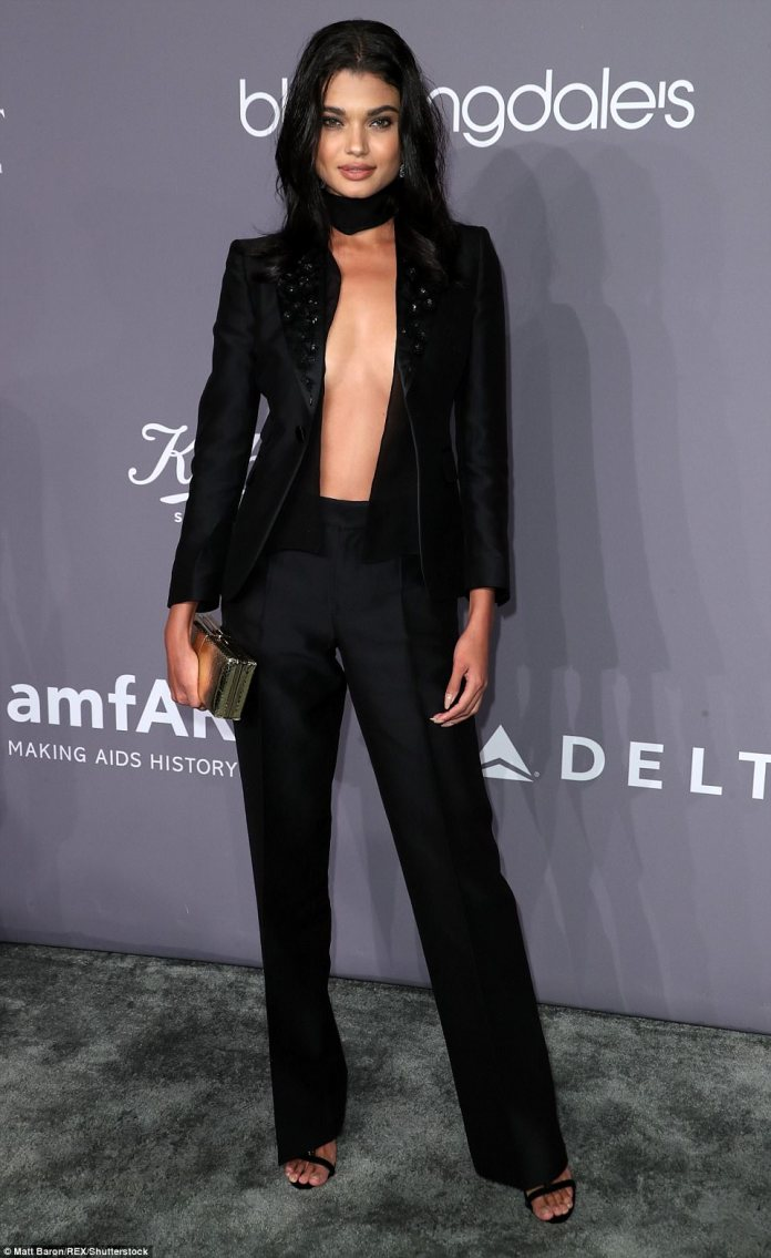 Daniela Braga, 26, went topless under a tailored black jacket with matching tuxedo pants and black sandal heels