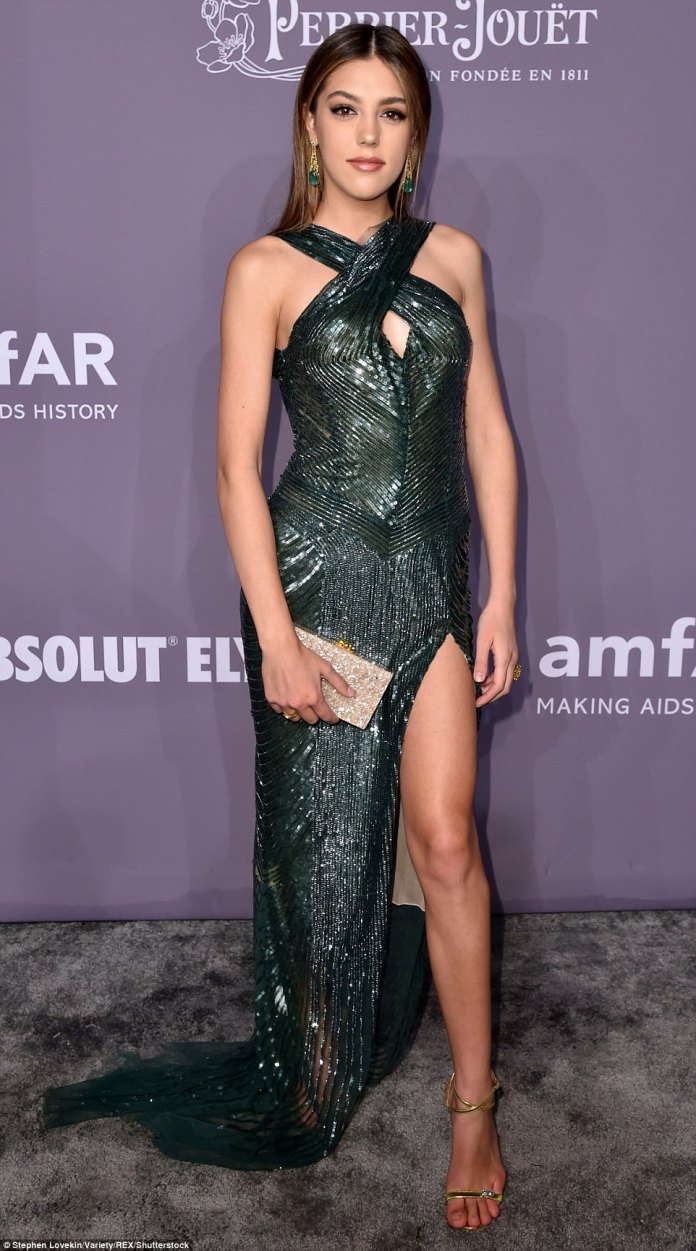 Sylvester Stallone's daughter Sistine Rose, 19, put on a show in a sleeveless peek-a-boo gown slit to the hip with emerald and gold chandelier earrings and gold sandal heels
