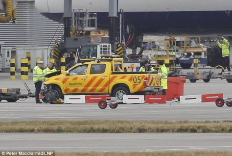 Police stand around an airport vehicle on the Tarmac at London Heathrow Wednesday morning