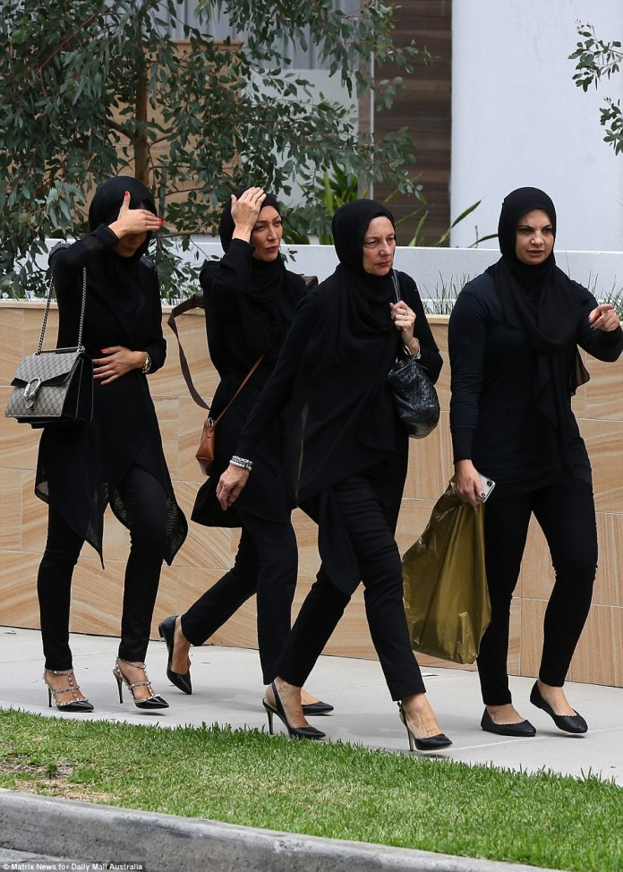 One woman was seen covering her face as she walked with other female mourners in Sydney on Thursday afternoon