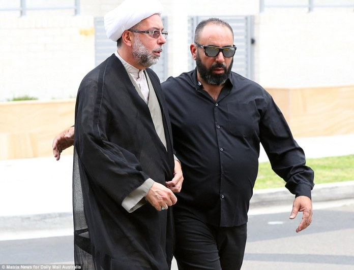 One man conversed with another, who appeared to be the Imam running Hawi's service