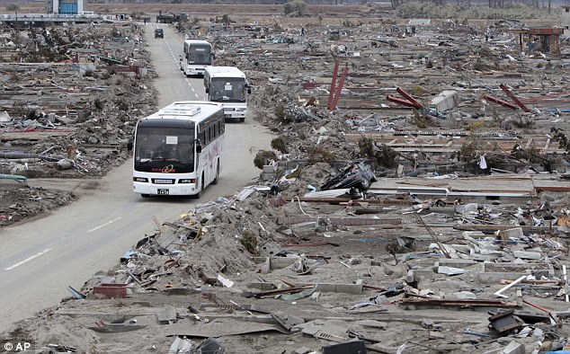 Destruction: A bus takes people past a flattened suburb in Miyagi Prefecture two weeks after the disaster in March 2011
