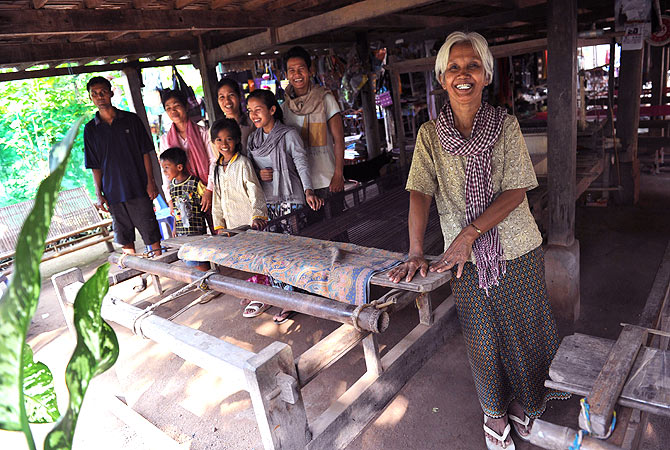 Cambodian grandmother Pres Noun (R), 68, poses with her children and grandchildren beside wooden looms at the family's silk farm in Prek Bongkong village. ? AFP Photo