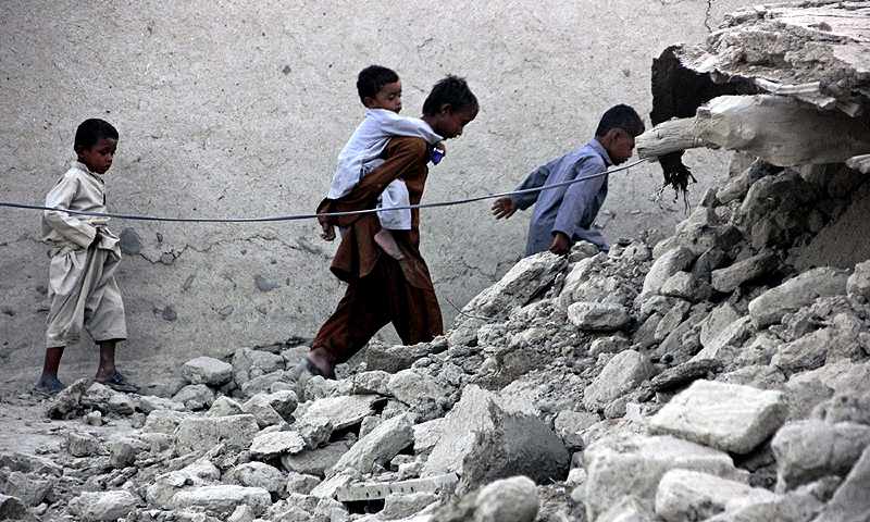 Survivors of the earthquake walk on rubble of a mud house after it collapsed following the quake in the town of Awaran.—Photo by Reuters