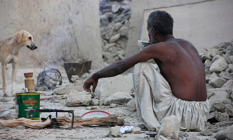 A survivor of an earthquake sits as he takes tea on the rubble of a mud house after it collapsed following the quake in the town of Awaran. - Reuters Photo
