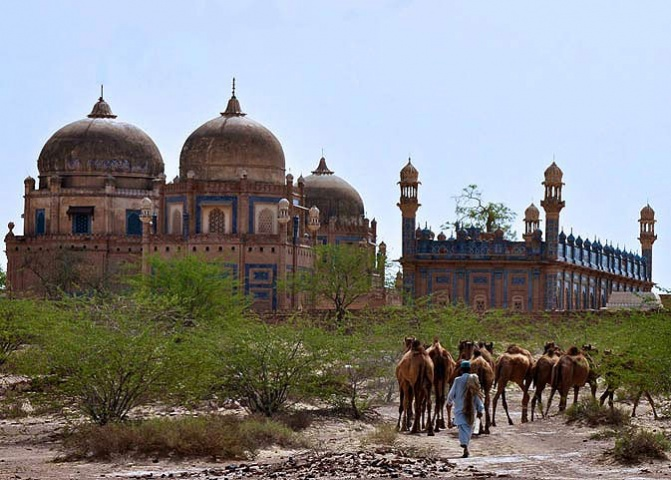 A camel herder leads his camels through the front of the royal graveyard of the Abbasi family. The Abbasi family was the ruling Nawab family of Bahawalpur and all previous Nawabs are buried here.