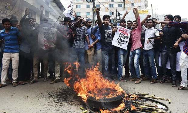 Bangladeshi students block the road and stage a protest following the murder of a law student, hacked to death by four assailants the night before, in Dhaka on April 7, 2016. —AFP
