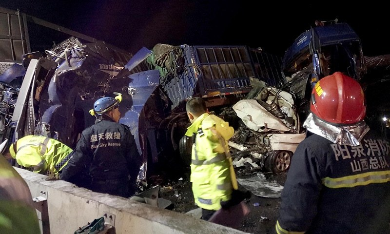 Rescue and other officials gather at the site of a huge pile-up on a Chinese motorway. ─AFP