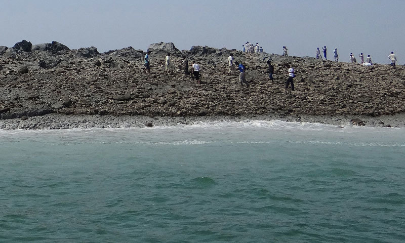 Men walk on an island that appeared 2 kilometres off the coastline of Gwadar on September 25, 2013, after an earthquake the day before. —AFP/File