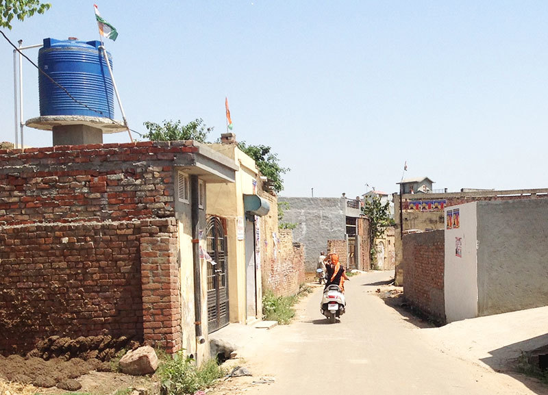 Hocus pocus: This picture of a Punjabi village in India has only two differences – Indian flags and women on bikes.
