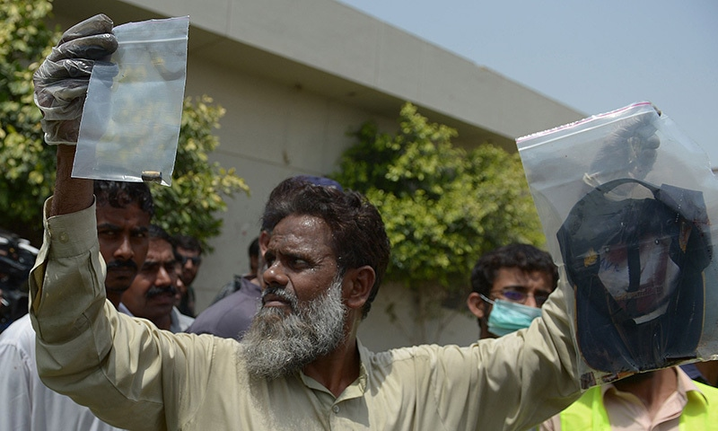 A plain-clothes police official holds up evidence collected from the scene of an attack by gunmen on a bus carrying Shias in Karachi on May 13, 2015.— AFP
