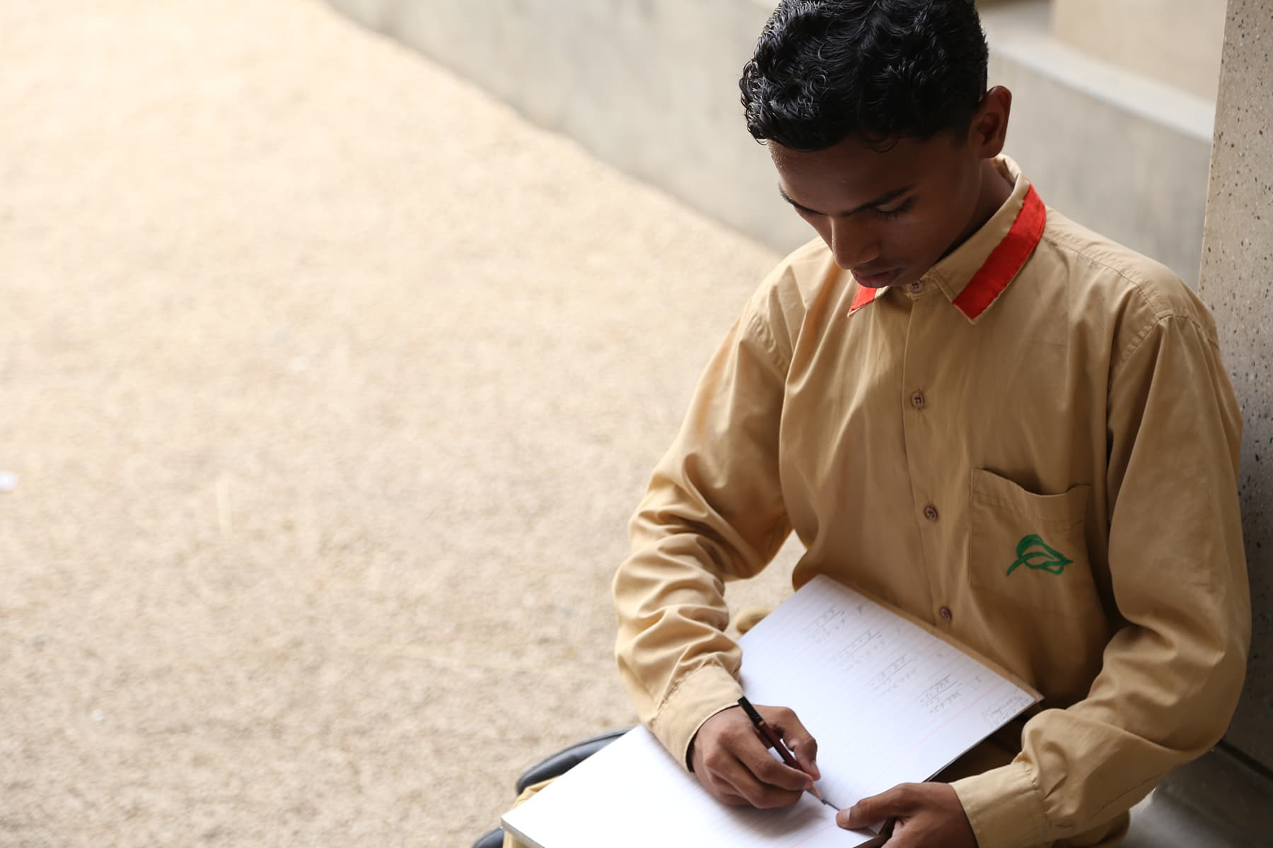 Khalil Ahmed pictured taking notes at his school - Photo by Mustafa Ilyas