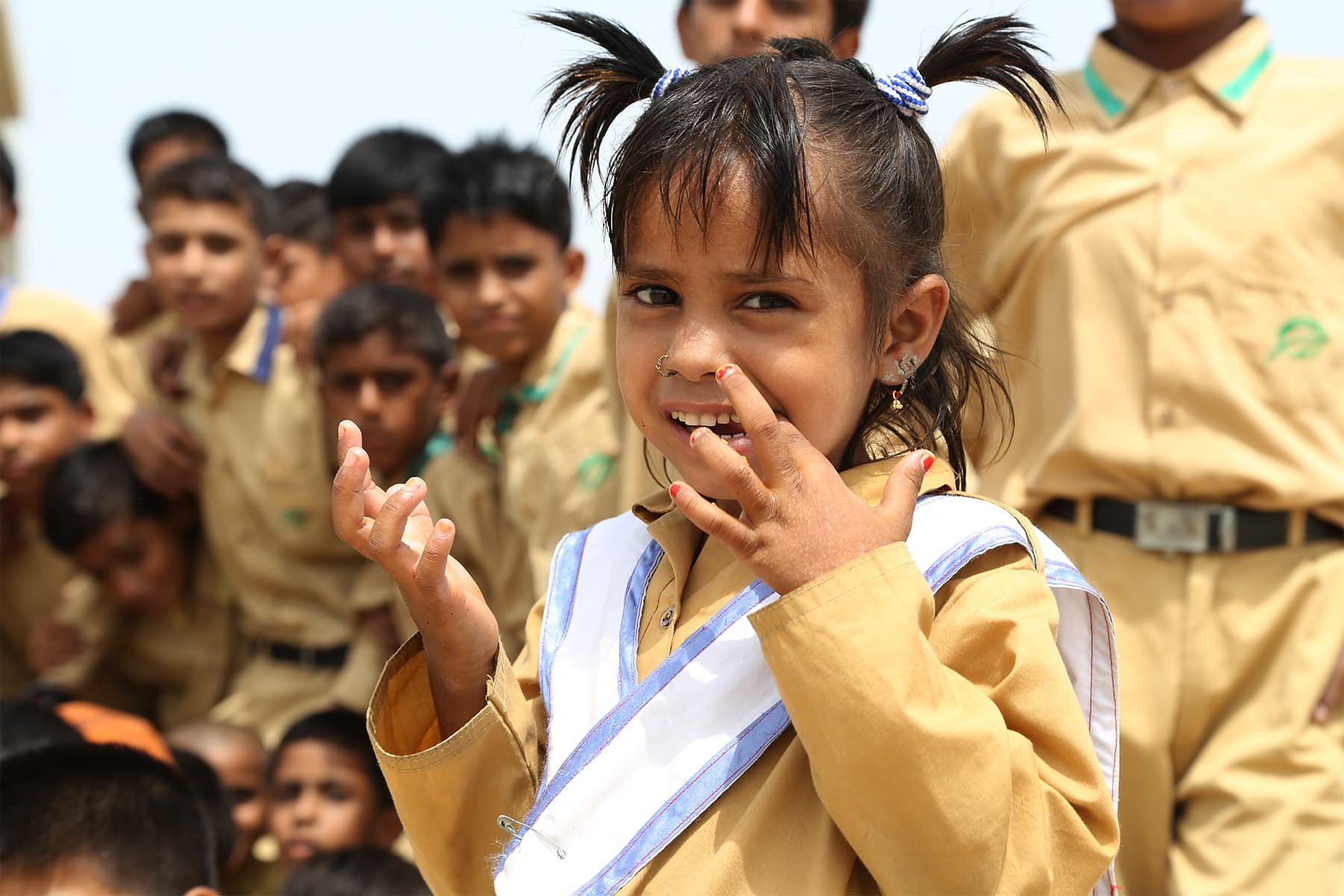A little girl who is a student at the TCF Gambat school smiles for the camera. - Photo by Mustafa Ilyas