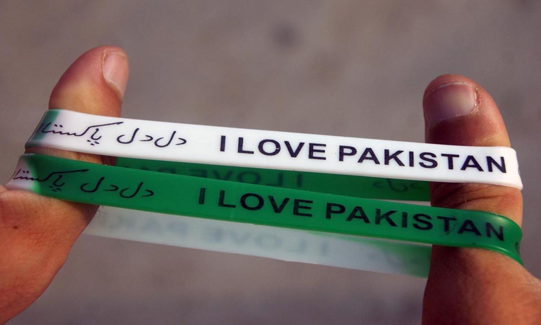 ایبٹ آباد میں نوجوانوں نے پاکستان سے محبت کے اظہار کے لیے ہاتھوں میں سبز اورسفید بینڈز پہنے—۔فوٹو/ آن لائن