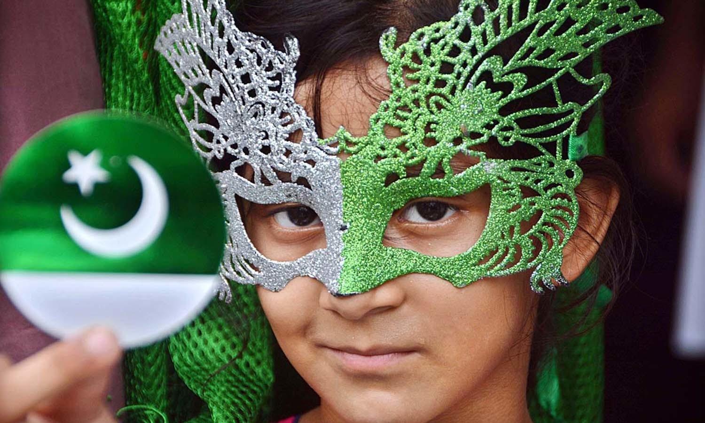 لاڑکانہ میں ایک بچی نے سبز اور گرین رنگ پر مشتمل ماسک پہن رکھا ہے —۔فوٹو/ اے پی پی