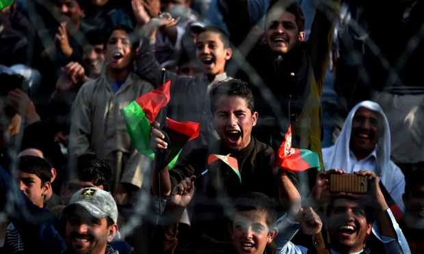 Afghan cricket fans cheer and wave the national flag as they welcome the country's cricket team home at the Cricket Board Stadium in Kabul. — AFP