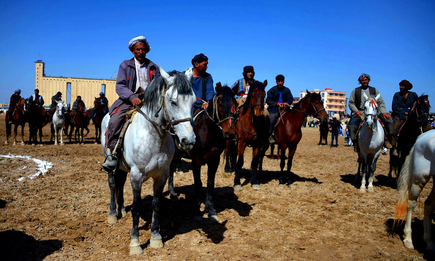 Afghan horsemen look on as others compete for a veal carcass during a game of buzkashi during celebrations for the Persian New Year. ─ AFP