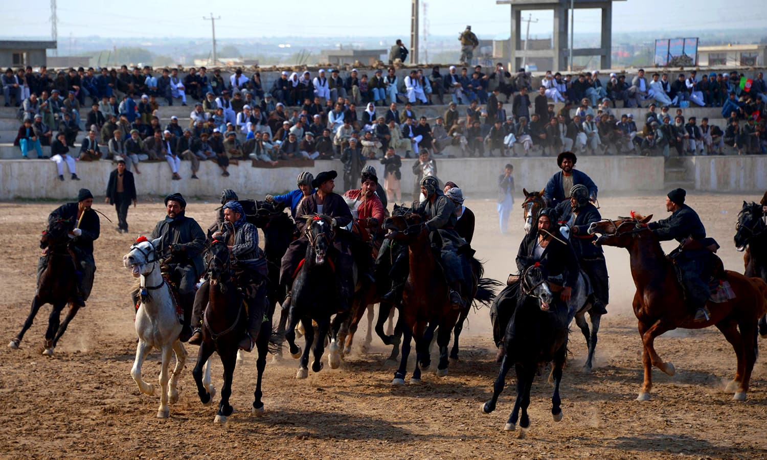 Horsemen compete for a veal carcass in buzkashi. ─ AFP