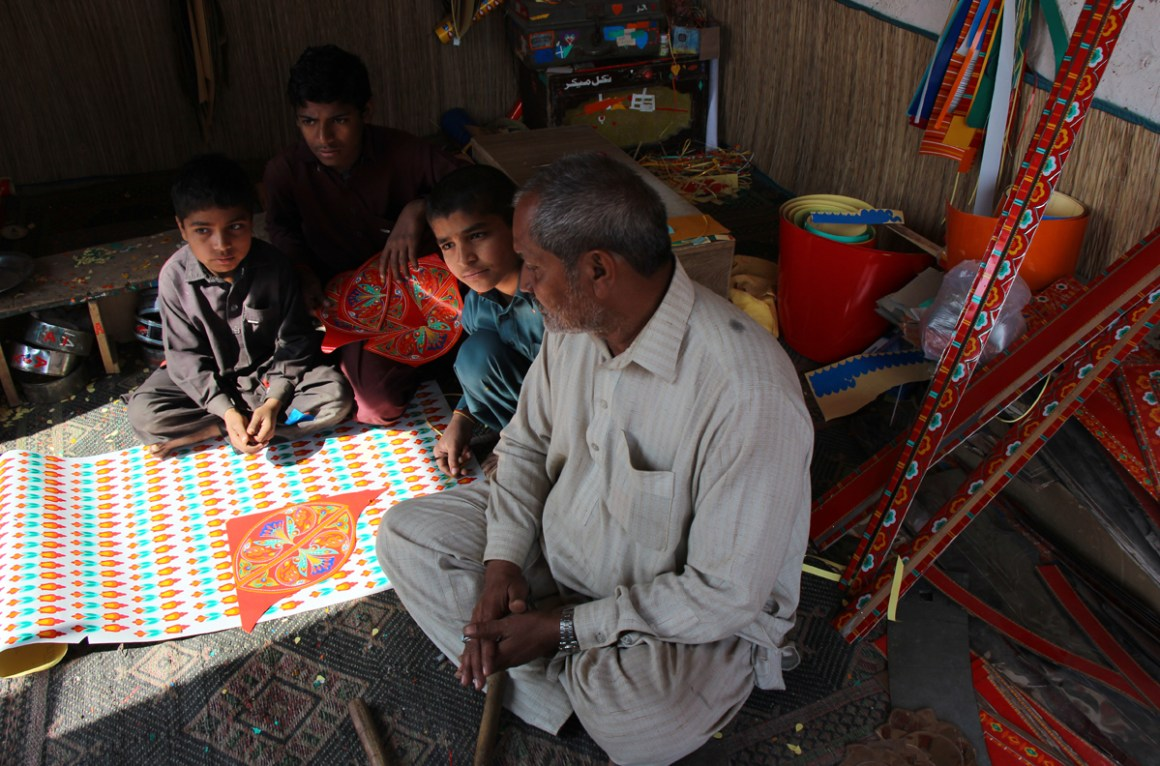 Manzoor Chamak Patti Wala sits with his apprentices at his workshop in Dera Ghazi Khan