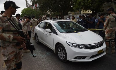 Rangers personnel inspect Amjad Sabri's bullet-riddled car.