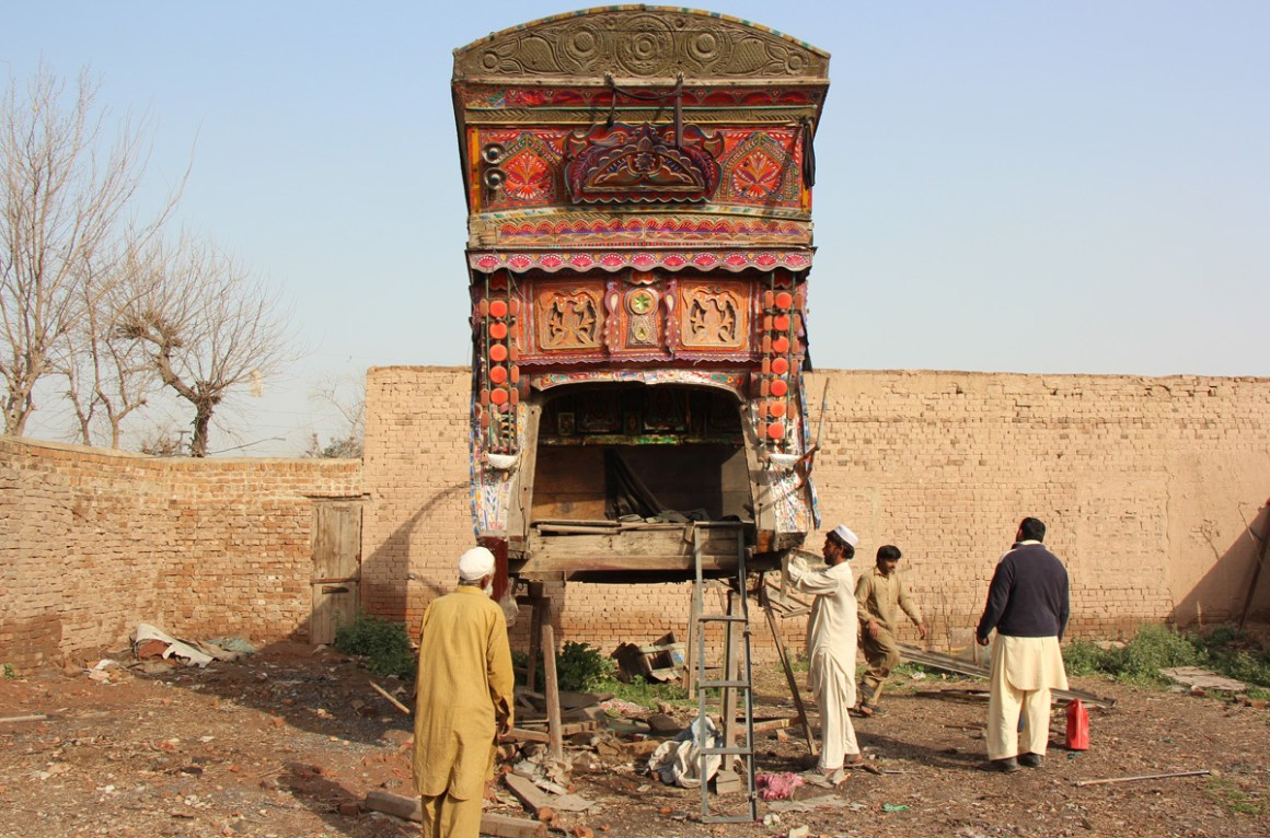 Labourers repair the body of a truck in Peshawar