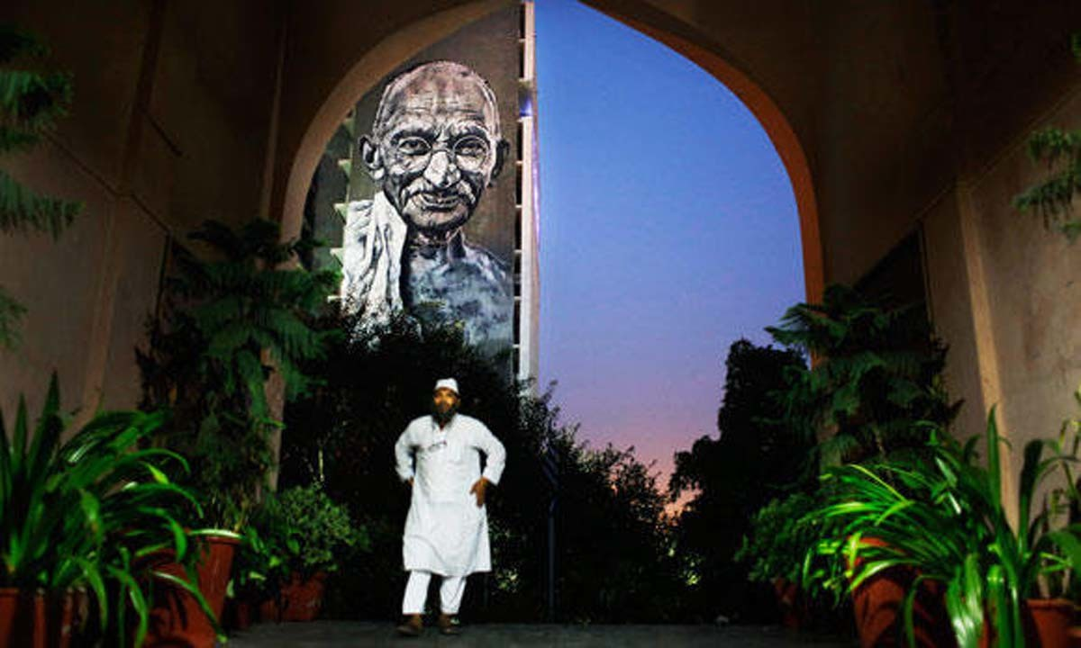 An Indian Muslim man walks into a mosque in New Delhi. A portrait of Mahatma Gandhi hangs on the wall of the  Delhi Police Headquarters in the background   AP