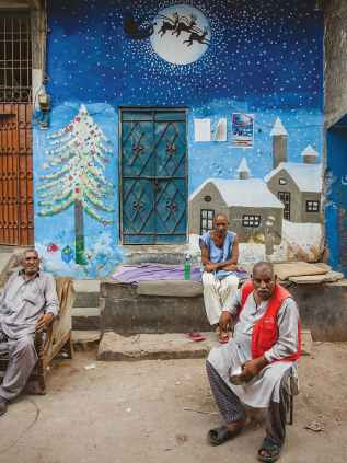 Men sit in front of a Christmas mural painted on a wall in Essa Nagri, Karachi | Mohammad Ali, White Star