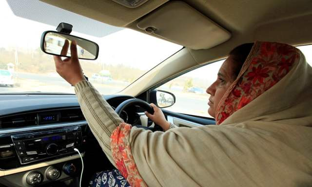 """Yasmin Perveen, one of the pioneer women """"captains"""" of Careem, adjusts back mirror while driving her car in Islamabad on Dec 7. ─ Reuters"""
