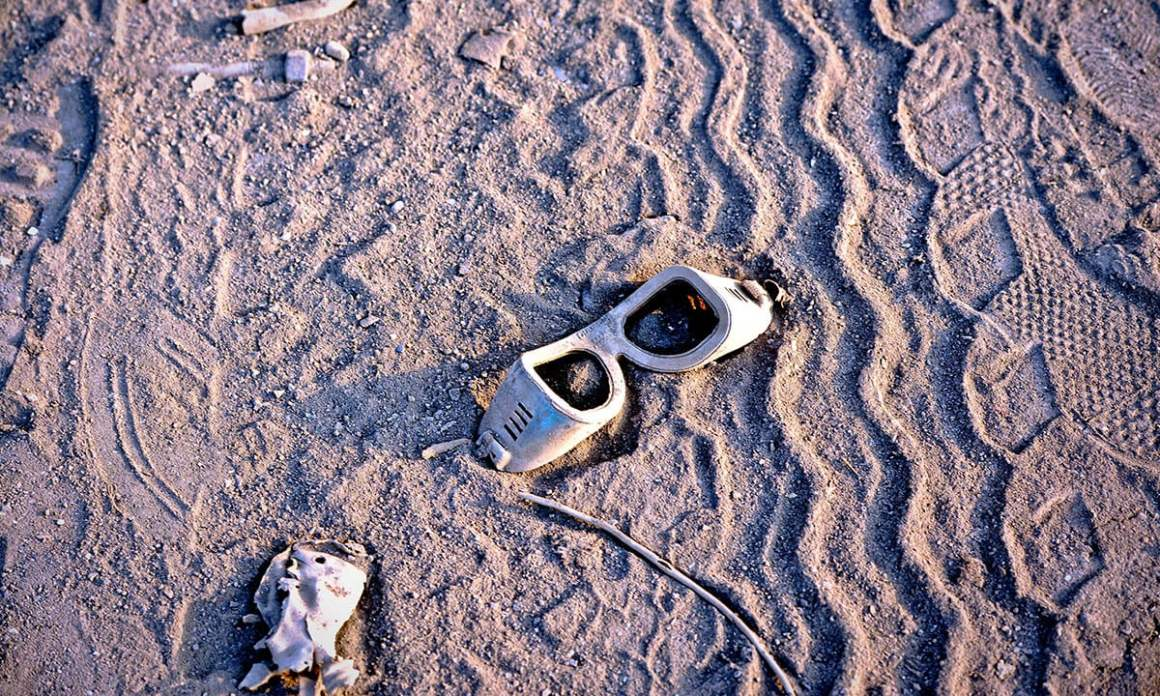 Discarded safety goggles lie in the sand. Credit: Herald/White Star