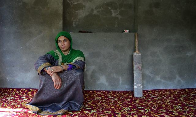Haleema Bano, mother of slain Amir Nazir Wani, seated next to the bat her son would play with at her home in Kakapora village