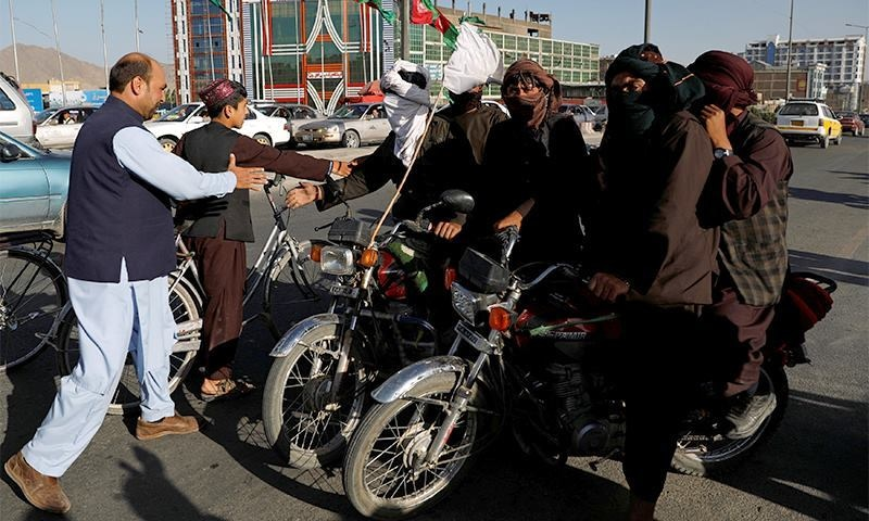 Taliban on motorbikes shake hands with people in Kabul during the ceasefire. ─ Reuters