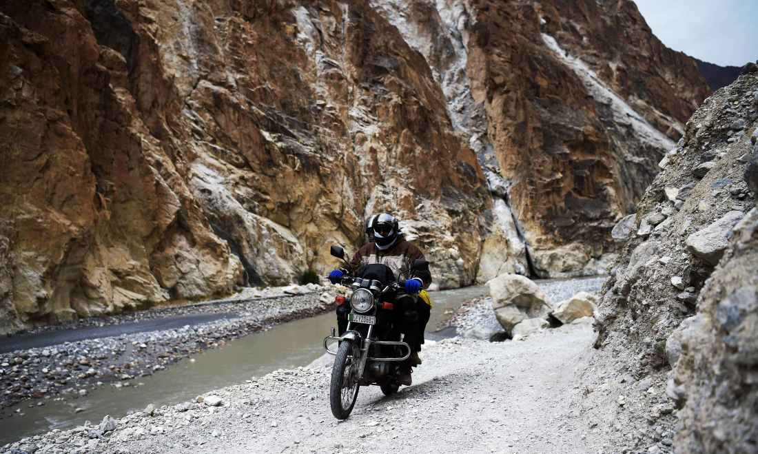 Tourists ride on a motorbike through Shimshal road of Hunza district. —AFP